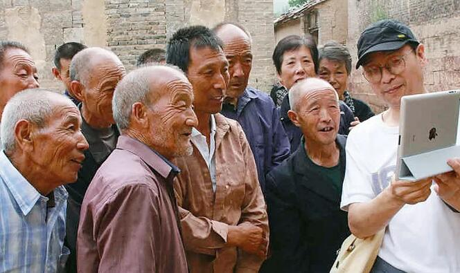 2011年,第一届许村国际艺术节期间,艺术家杨迎生与村民互动。