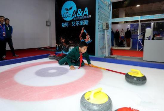 资料图:小学生在北京文博会上体验冰壶运动
