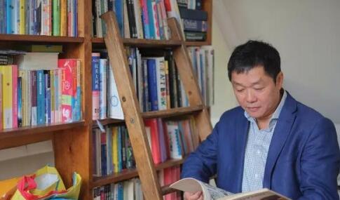 王坚在自家的书架前(华闻派微信公众号)