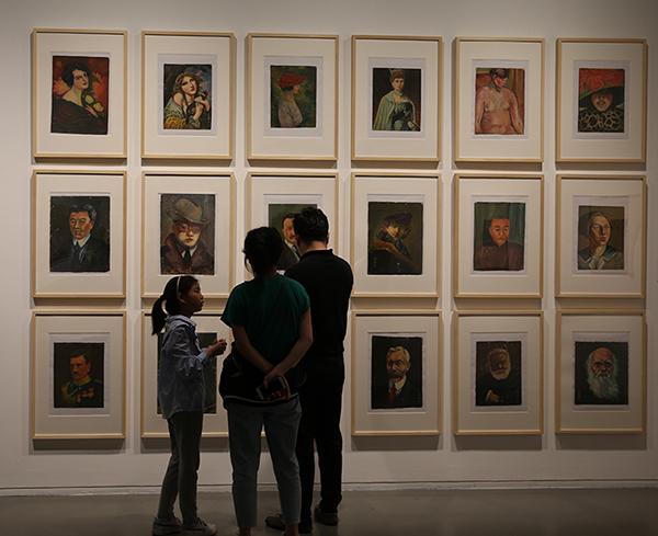 展览现场,背景为郑慕康作品《18件上海美专函授作业·人物习作》
