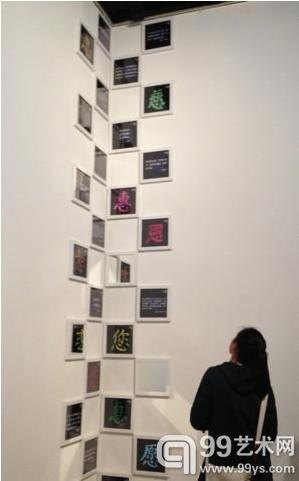 """图为一名年轻女性在欣赏墙体上的""""多元汉字"""""""