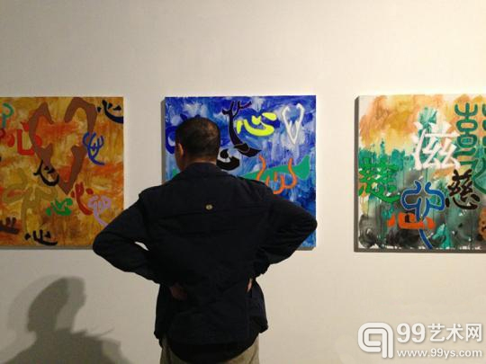 图为观众在品味皮明《心届》多媒体汉字展的作品
