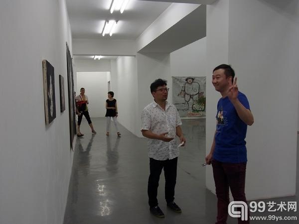 艺术家廖国核(左)与友人在展览开幕现场